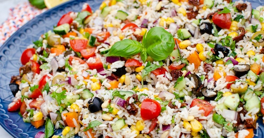 Italian Style Rice Salad on a large blue platter plate and basil leaves on top