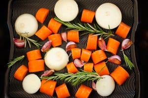 Chopped onions, carrots, garlic cloves and sprigs of rosemary in a roasting tin