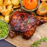 Slow Cooked Leg of Lamb on a wooden chopping board served with flawless Yorkshire puddings, roast potatoes, carrots ,peas and gravy and garnished with rosemary