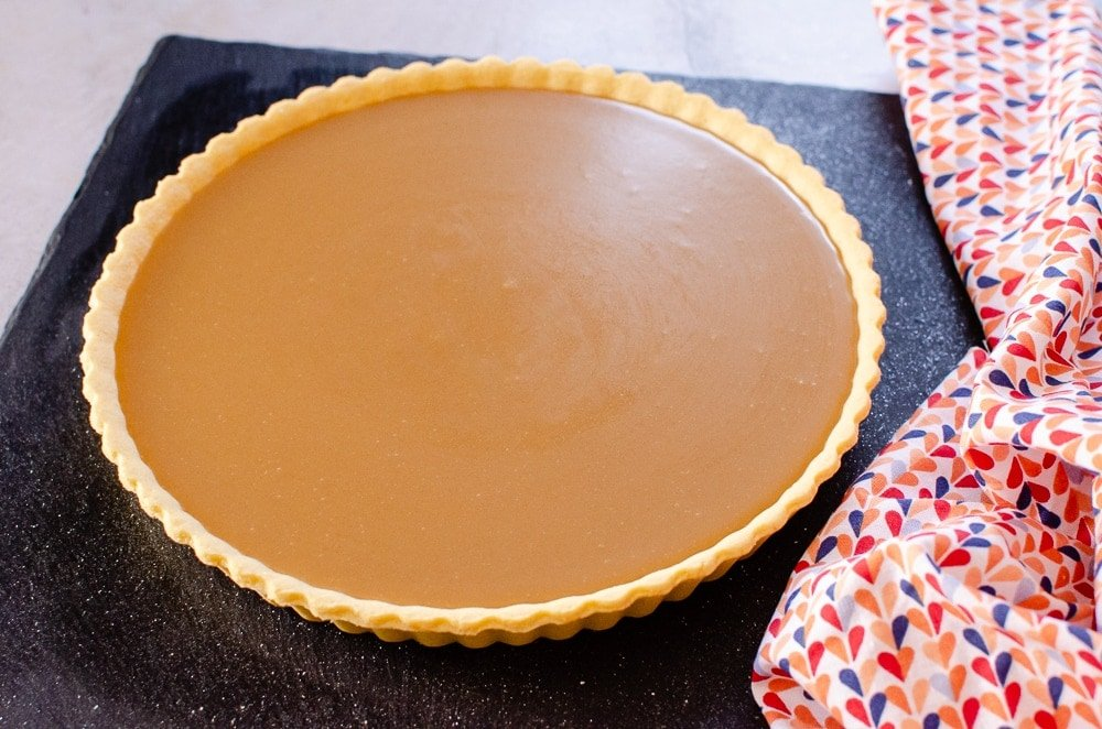 Old School Butterscotch Tart on a black slate plate with a multi colour towel on the side