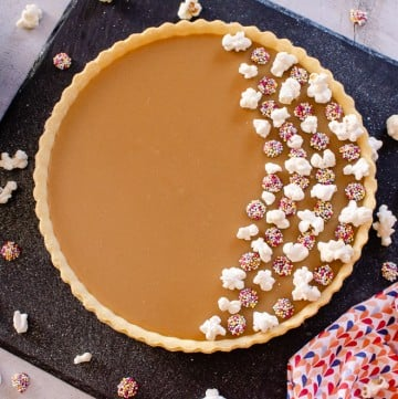 Old School Butterscotch Tart decorated with toffee popcorn and milk chocolate jazzies on black slate