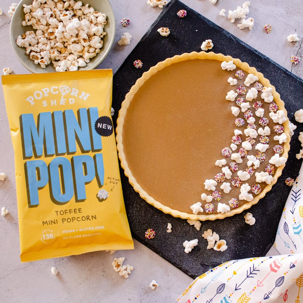 Old School Butterscotch Tart decorated with toffee popcorn and milk chocolate jazzies on black slate served with a bowl of toffee popcorn and the bag of mini pop on the side