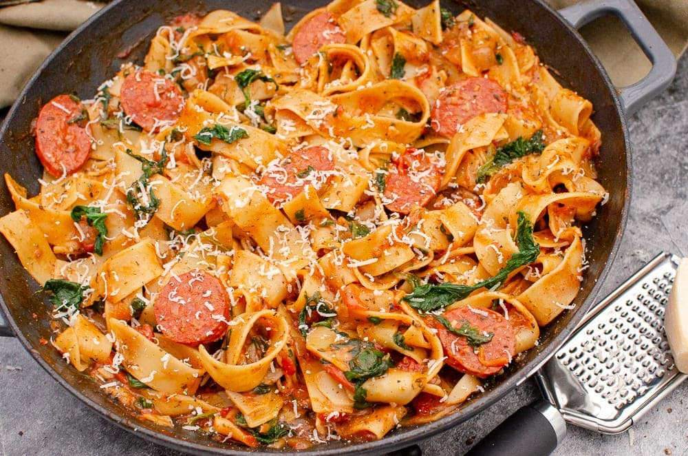 Quick and easy Chorizo and Tomato Pappardelle Pasta with Parmesan and silver cheese grater on the side