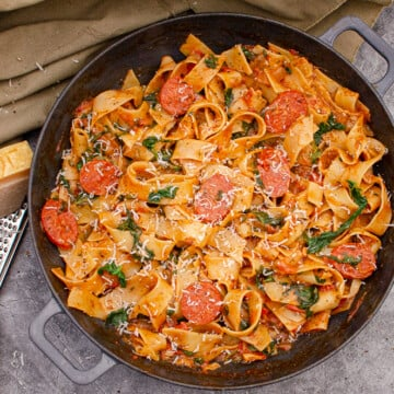 A simple recipe of Chorizo and Tomato Pappardelle Pasta with Parmesan and silver cheese grater on the side