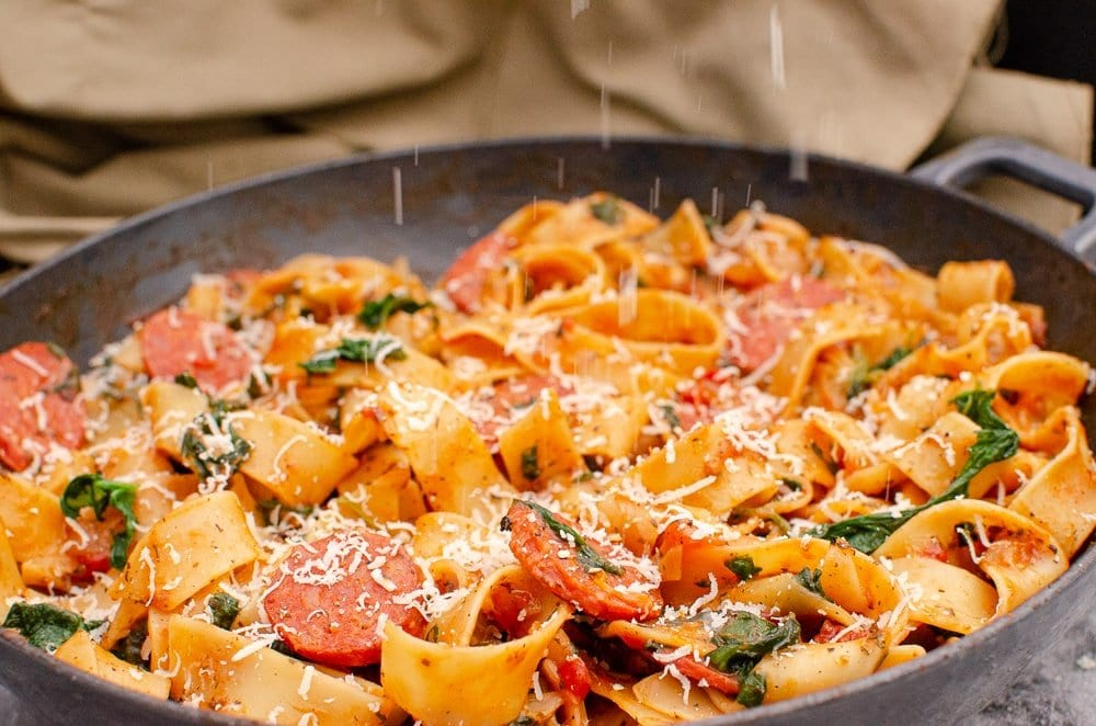Grating Parmesan over our Chorizo and Tomato Pappardelle Pasta in a cast iron pan