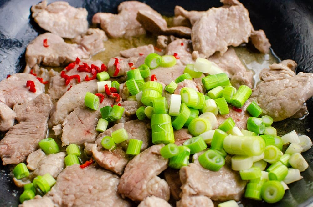 Chopped spring onions and rec chillies added to the pork slices cooking in a cast iron pan