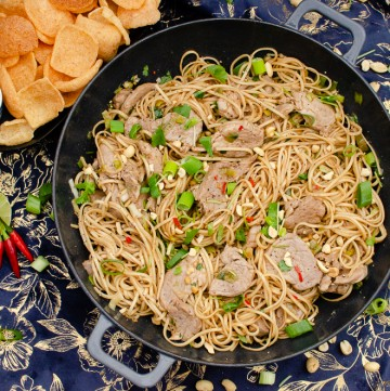 Asian Spicy Pork Noodles in a cast iron pan garnished with chopped coriander and unsalted peanuts with Thai crackers served on the side