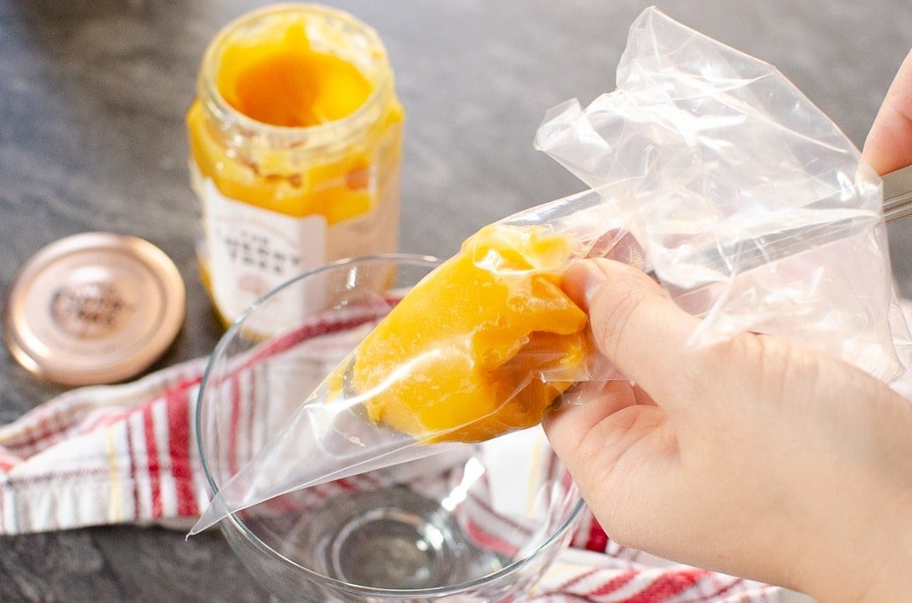 Passion fruit curd being put into a clear piping bag