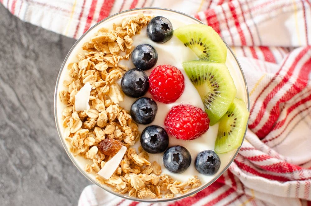 Tropical Granola Yoghurt with blueberries, raspberries and kiwi in a glass bowl