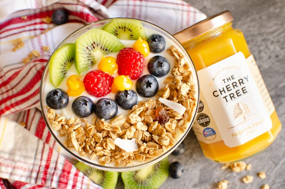 Tropical Granola Yoghurt with Fruit with a red and white striped towel and a jar of the cherry tree curd in the background