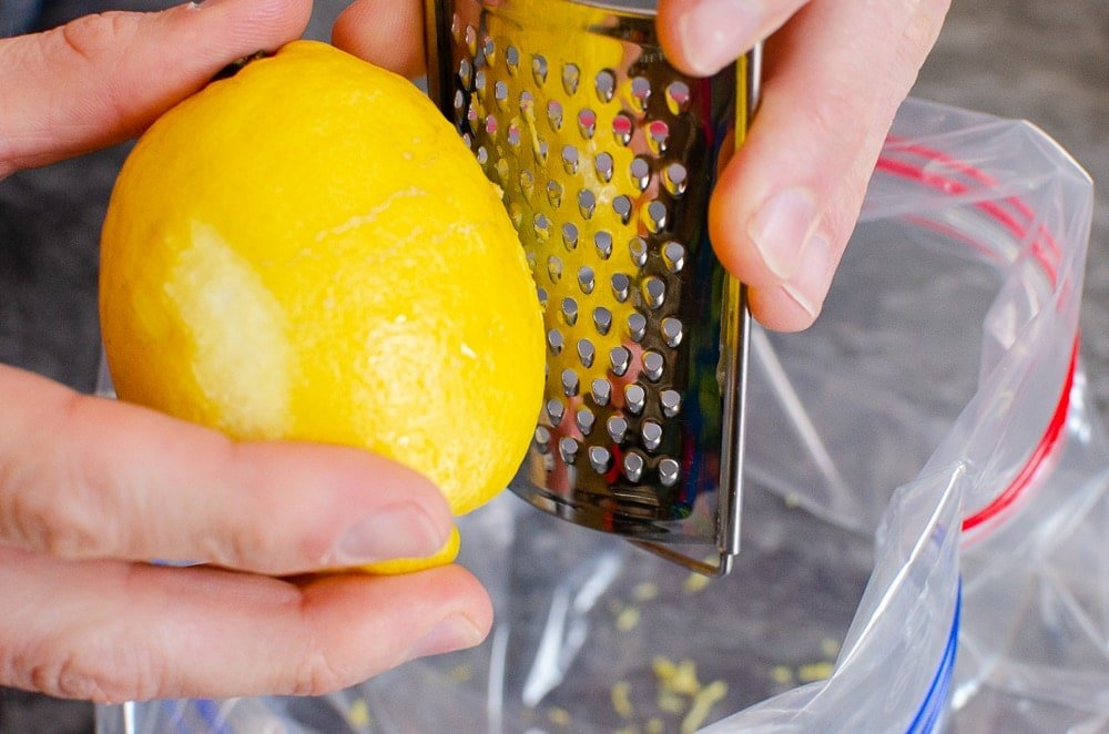Grating lemon zest with a silver grater into a clear plastic sandwich bag