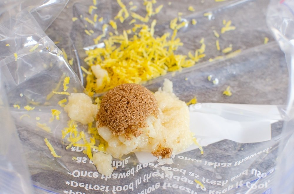 Lemon zest, dark brown sugar and garlic in a clear plastic zip bag