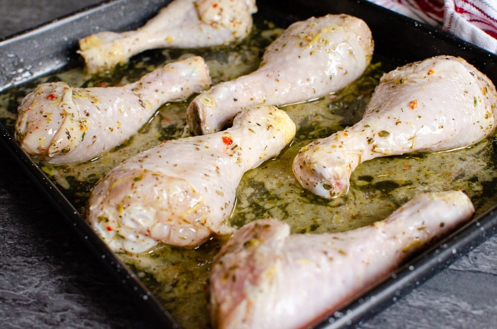 Chicken drumsticks on a black baking tray ready to cook