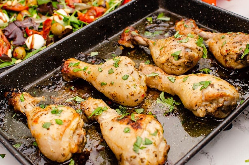 Zesty Italian Chicken Drumsticks garnished with chopped basil on a black baking tray