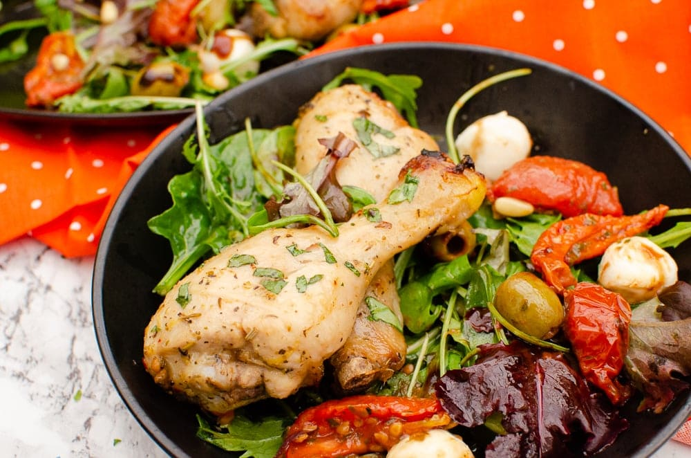 Zesty Italian Chicken Drumsticks served with salad in a black bowl