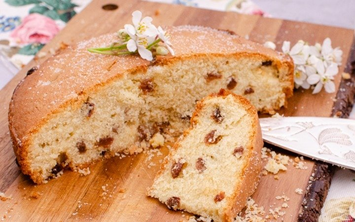 Manor House Sultana Cake served up on a wooden board decorated with white flowers