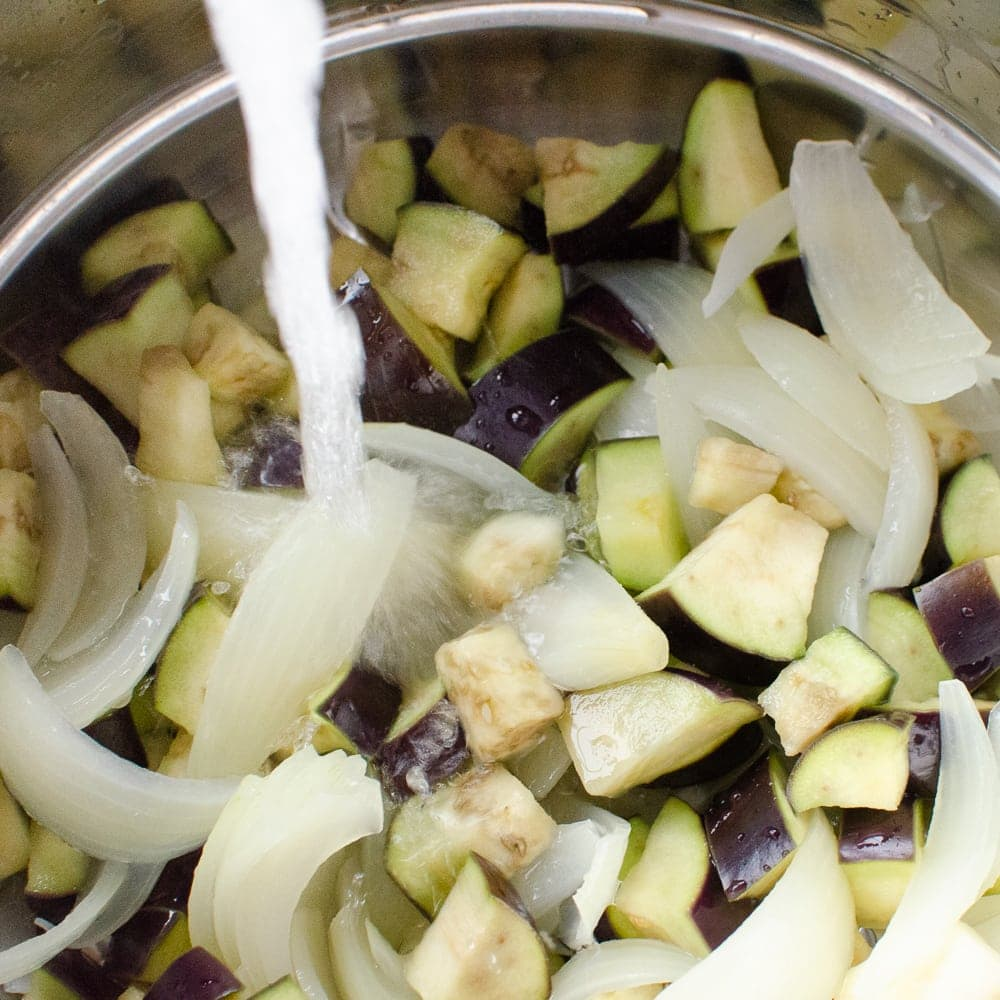 Chopped onion and aubergine being cooled down with cold water in a silver colander