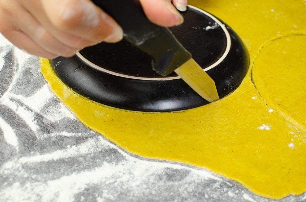 Cuttting out circle shapes in our pastry witha black plate to make our Jamaican beef patties