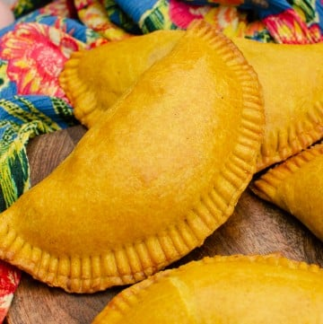 Jamaican Beef Patties on a brown chopping board with a blue and pink flower Caribbean cloth on the side