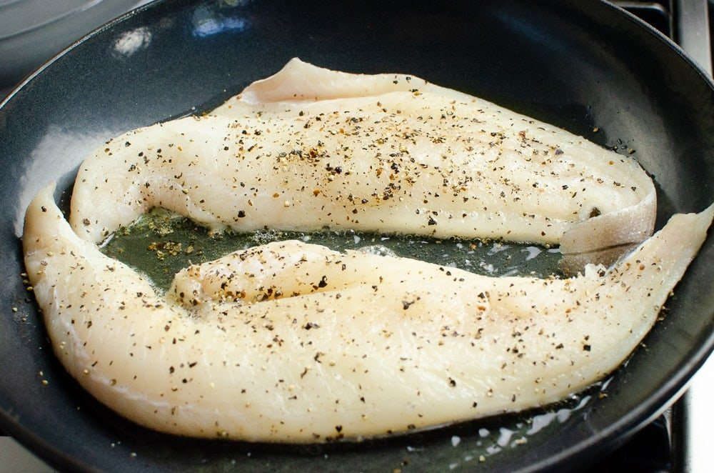 Two haddock fillets cooking in a black cast iron pan