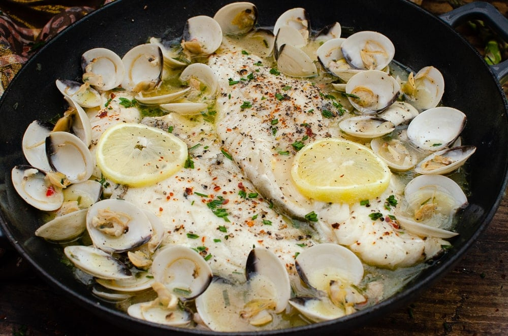 Haddock and Clams in Garlic and Wine Sauce in a cast iron pan