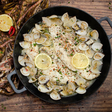 Haddock and Clams in Garlic and Wine Sauce in a cast iron pan on a wooden table with lemon and red chillies on a brown and pink towel