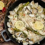 Haddock and Clams in Garlic and Wine Sauce on a wooden table with lemon and red chillies on a brown and pink towel