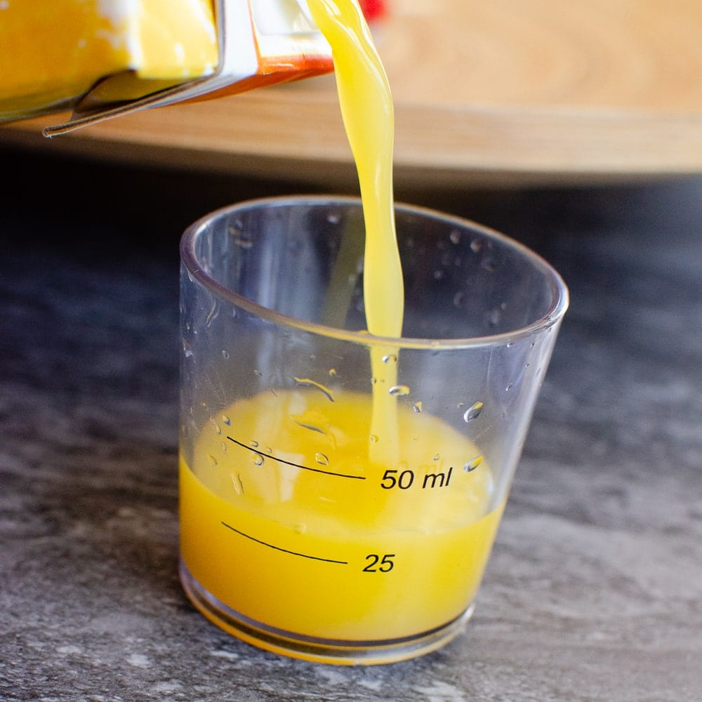 Fresh orange being poured into a measuring cup