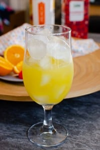 Orange mixture with ice cubes in a glass with oranges in the background on a round wooden bowl