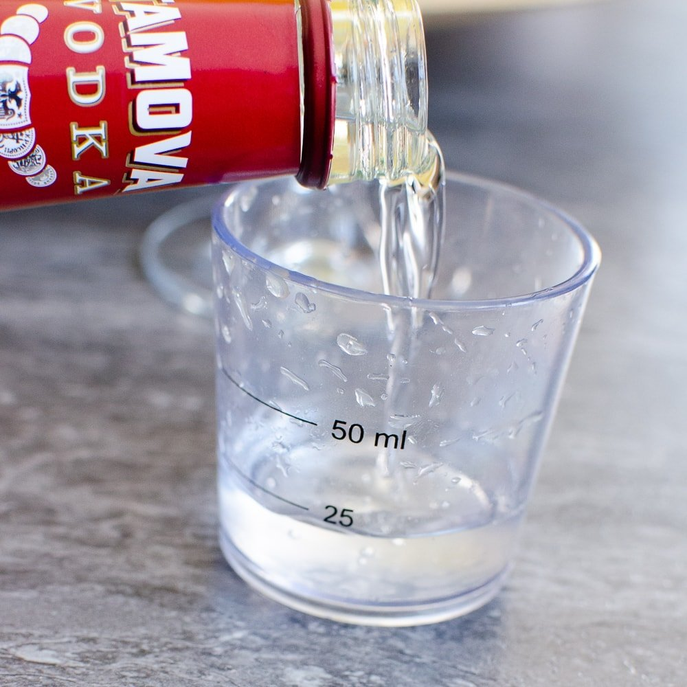 Vodka being poured into a 50 ml measuring cup