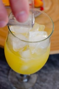 Pouring the vodka over the ice and orange mixture in a glass