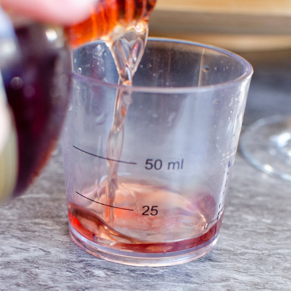 Chambord Liqueur being poured into a 50 ml measuring cup