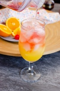Cranberry and Chambord liqueur being poured over ice and orange juice mix in a hurricane glass