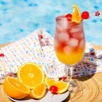 Sex on the Beach Cocktail floating on a wooden bowl in a swimming pool with sliced orange with cherries and a white towel with blue, yellow and pink triangles.