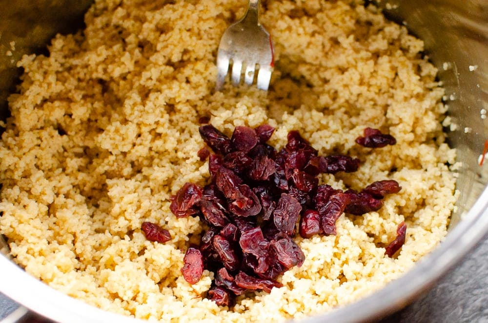 Adding dried cranberries to the couscous in a silver pot