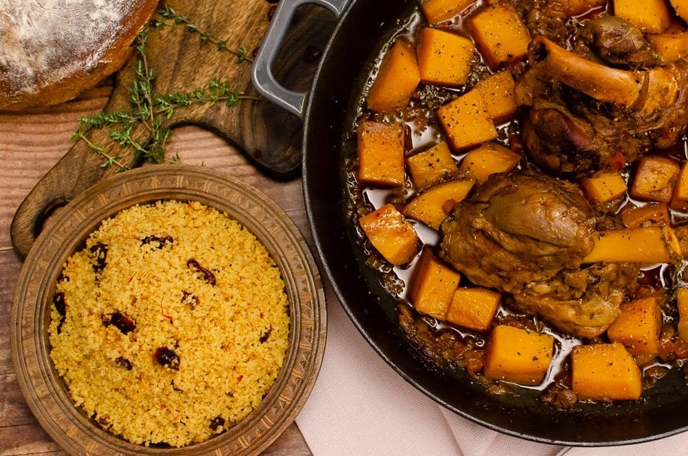 Persian Saffron Couscous in a brown bowl and our Persian Lamb Shanks and butternut squash in a cast iron pan