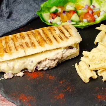 Tuna and Cheese Melt Panini on black slate with crisps and salad on the side