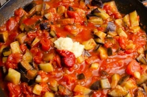 Aubergine, chopped tomatoes cooking in a cast iron pan with Garlic and chilli puree on top