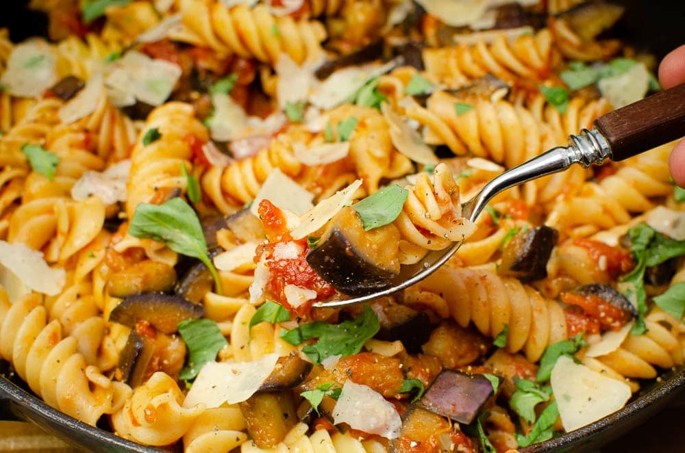 Pasta alla Norma being picked up with a silver spoon ready to eat