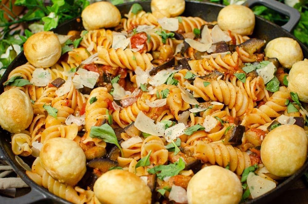 Pasta alla Norma with chopped basil and Parmesan flakes on top and garlic dough ball served around the edge of the pasta dish in the cast iron pan