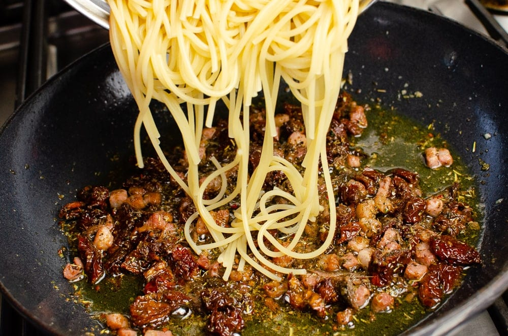 Placing spaghetti ontop of chopped pancetta and sundried tomatoes in olive oil