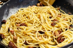 spaghetti with lumps of pancetta and chopped sundried tomatoes in a black cast iron