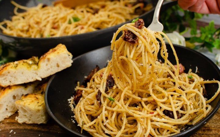 Pancetta, Anchovy & Sundried Tomato Spaghetti served in a black bowl and being scooped up with a silver fork