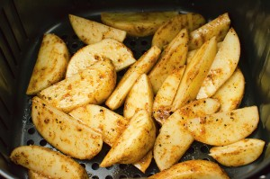 curried wedges in the air fryer ready to be cooked