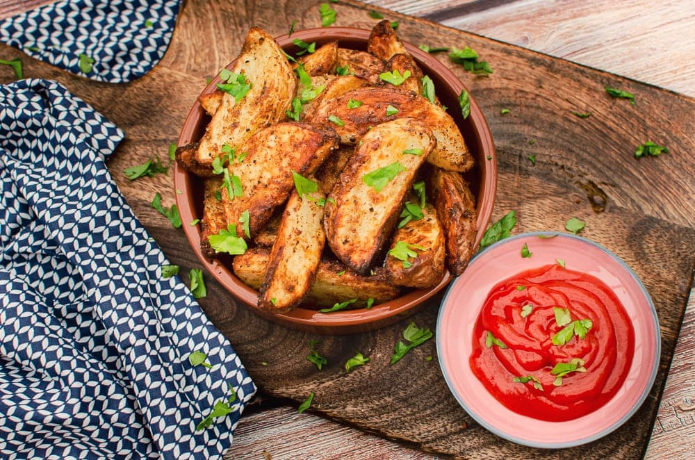 Spicy Curried Potato Wedges covered in chopped parsley a tapas dish with ketchup served for dipping on the side