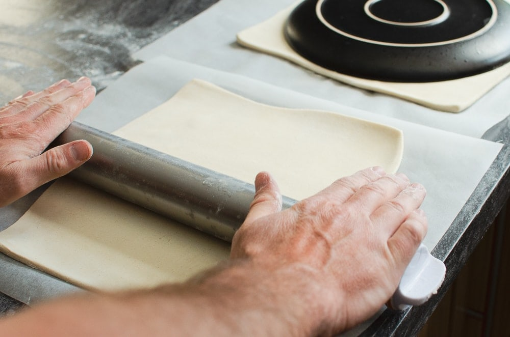 Rolling out the block of puff pastry with a silver rolling pin