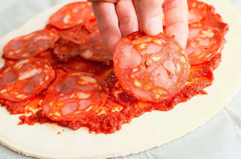 Placing down chorizo slice on top of the Gia garlic and tomato puree on puff pastry