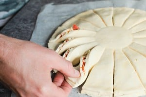Twisting the the cut puff pastry segments to form the wheel shape