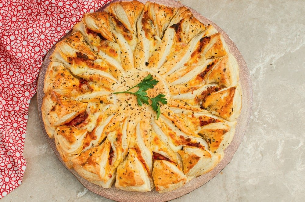 Puff pastry pizza wheel on a wooden board with parsley leaves in the middle