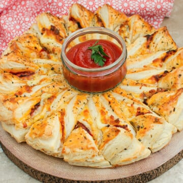Puff pastry pizza wheel with a glass bowl filled with ketchup in the middle of the wheel to dip in your segments
